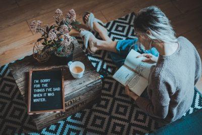 絨毯の上で本を読む女性