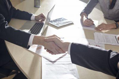 机越しに握手する男性二人