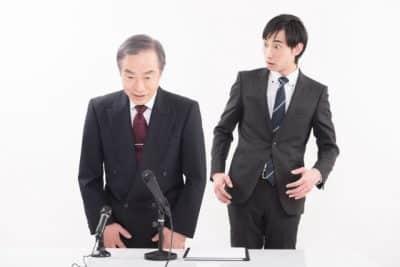 記者会見の上司と部下