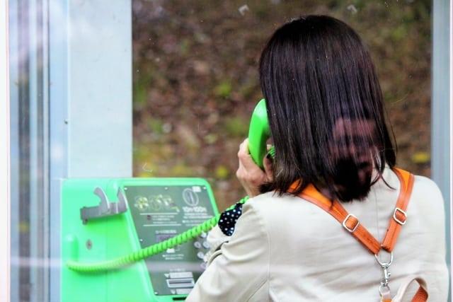 公衆電話で話す女性