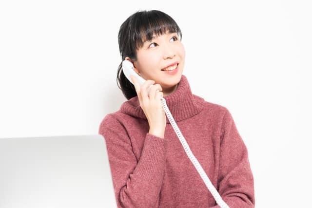固定電話で話す女性