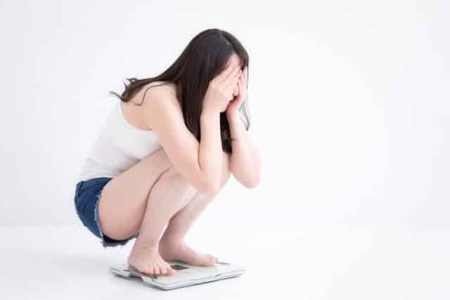 体重計の上で落ち込む女性