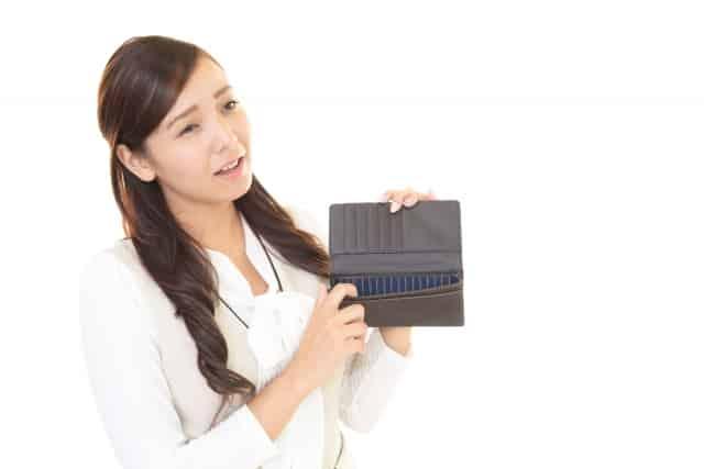 空の財布を見せる女性