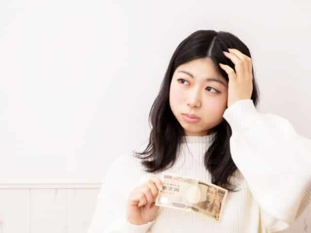 1万円札を手に頭を抱える女性