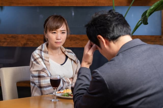 男を問い詰める女性