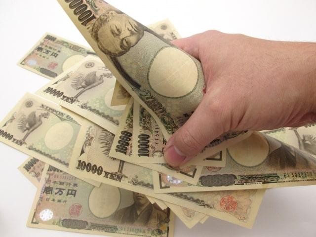 一万円札をつかみ取りする手