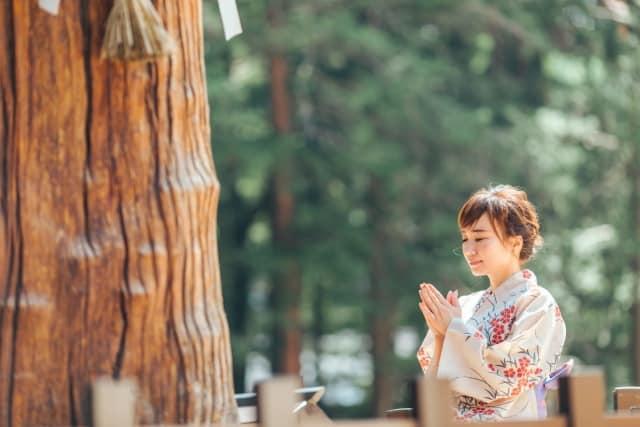御神木に手を合わせる女性