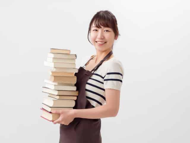 本を抱える女性書店員